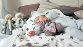 Child sleeping on parents` bed in a cozy atmosphere in the house, little boy asleep hugging a stuffed toy, sweet baby stock video