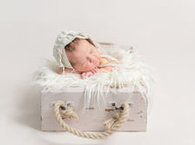 Child sleeping on rustic box, wearing hat Stock Images