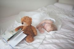 The child sleeps on the bed of an adult. stock photo