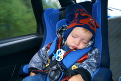 The child sleeps in the car. The baby in autumn clothes sits in a children's autoarmchair and sleeps Royalty Free Stock Images
