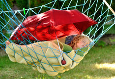 Child sleeps in a hammock. Stock Photo