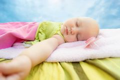The child sleeps on the street in a children`s towel, against the sky, the nipple lies nearby. Wide-angle photo stock image