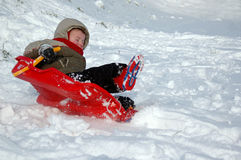 Child sleighing in Snow. Small boy (3) on a sleigh sliding down a snowy hill Stock Image