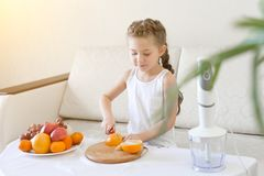 The child slices an orange with a knife royalty free stock photo