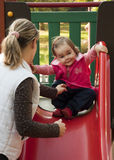 Child on a slide. Little girl on a top of a red slide smiling; her mother helping and securing her Stock Photos