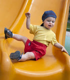 Child on a slide. Small child on a yellow slide in an outdoors playground Royalty Free Stock Images
