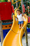 Child On Slide. A cute young kid playing on a slide in a park stock photo