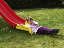 Child on a slide. Child on a red and yellow slide Royalty Free Stock Images