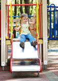 Child on slide outdoor in park. Stock Photos