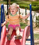 Child   on slide in playground.Outdoor park. Stock Image