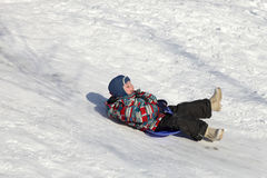 Child slides on a board Stock Images