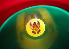 Child slides in multicolored tunnel slide Royalty Free Stock Image