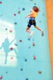 Child sliding down the climbing wall Stock Image