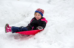 Child sliding down a frozen hill Royalty Free Stock Photos