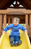 Child sliding down a sliding board. Stock Images