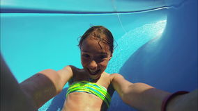 Child sliding down water slide in pool. Close up stock video