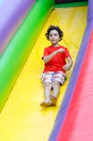 Child Sliding in an inflatable playground Royalty Free Stock Photo