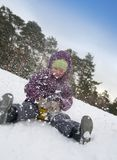Child sliding in the snow Stock Photography