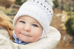A child in a sling at the mother`s under a jacket, a portrait of a baby in winter clothes Royalty Free Stock Image