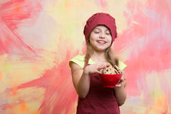 Child, small girl in red chef hat, apron with chocolate cookies Royalty Free Stock Photography