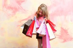 Child or small girl with shopping bag or present pack. On colorful background, holiday and party celebration stock image