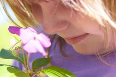 Child smelling flowers. Young girl smelling the subtle fragrance Royalty Free Stock Images