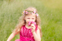 Child smelling pink rose Royalty Free Stock Photo