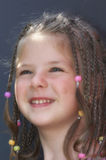 Child smile. Girl with beads in her hair Royalty Free Stock Photo