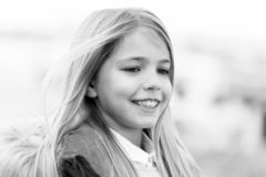 Child smile on blurred environment. Girl with blond long hair on aun day outdoor. Kid fashion and style. Happy childhood concept. Beauty, look, hairstyle royalty free stock photo