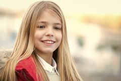 Child smile on blurred environment. Girl with blond long hair on autumn day outdoor. Happy childhood concept. Kid fashion and style. Beauty, look, hairstyle royalty free stock images
