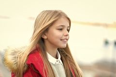 Child smile on blurred environment. Girl with blond long hair on autumn day outdoor. Happy childhood concept. Kid fashion and style. Beauty, look, hairstyle stock photo