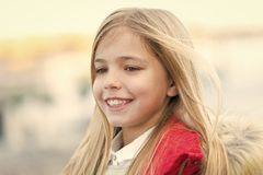 Child smile on blurred environment. Girl with blond long hair on autumn day outdoor. Kid fashion and style. Happy childhood concept. Beauty, look, hairstyle stock images