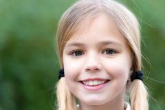 Child with smile on cute face on natural background, childhood. Child with smile on cute face on natural background. Little girl with blond hair ponytails stock photos