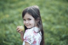 Child smile with green apple fruit on nature, food Royalty Free Stock Photo