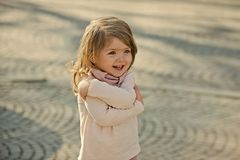 Child smile with hug hand gesture on sunny day. On grey pavement outdoor. Happy childhood concept stock photos