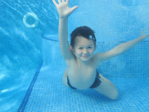 The child smile underwater. Under the water in the swimming pool Royalty Free Stock Images