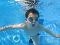 The child smile underwater. Under the water in the swimming pool Stock Images