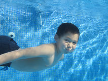 The child smile underwater. Under the water in the swimming pool Royalty Free Stock Photography