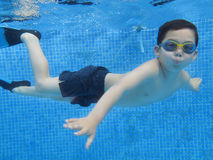 A child boy is swimming underwater in a swimming pool, with swimming glasses, with swim fins Royalty Free Stock Photos