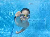 A boy is swimming underwater in a swimming pool, with glasses, holding breath, smiling, a fist pointing towards camera Royalty Free Stock Image