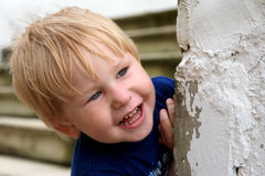 Child smiles. Child looks out from the wall and smiles Royalty Free Stock Photos