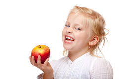 Child smiles happy with healthy fruit (apple) Royalty Free Stock Photos