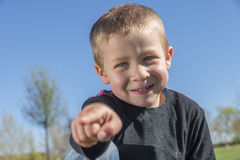 Child smiles at the park is pointing. At camera Stock Images