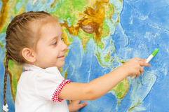 Child smiles by world map. Happy little girl smiles by world map stock photo