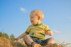 Child smiling against the blue sky. The little child smiling against the blue sky Royalty Free Stock Photos