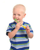 Child Smiling and Brushing His Teeth. On White Background royalty free stock photography