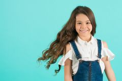 Child smiling with healthy brunette hair. Girl smile with flowing long wavy hair on blue background. Kid beauty salon concept. Haircare, hairstyle, hairdresser Royalty Free Stock Photography