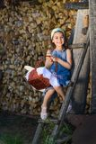 Child smiling with no teeth sitting near the wooden wall of the shed royalty free stock photos