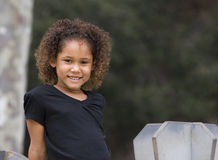 Child smiling in park. Portrait of a young girl of mixed racial heritage smiling while sitting in park royalty free stock photography
