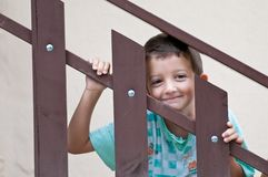 Child smiling through a railing Royalty Free Stock Image